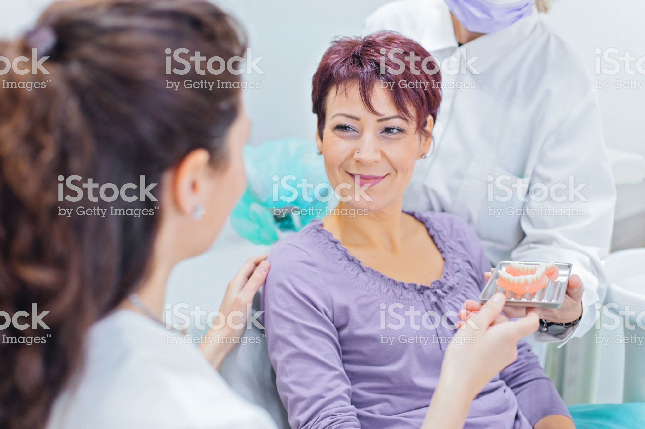 Female dentist talking to a patient and showing her teeth dentures
